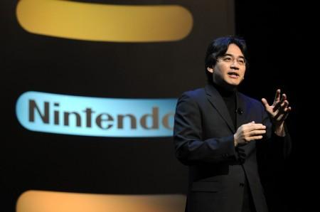 Nintendo president, ceo Satoru Iwata in black suit on stage giving a presentation